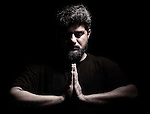 Dramatic portrait of a Middle eastern man with his hands folded in a prayer or meditation isolated on black background