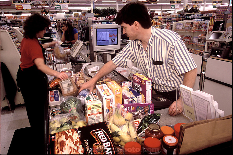Craig Caven of American Canyon, California going through the checkout counter as he is purchasing a weeks' worth of food for the upcoming food picture. He is shopping at Raley's, a California grocery chain. (Supporting image from the project Hungry Planet: What the World Eats.)