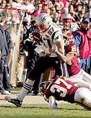 New England Patriots tight end Rob Gronkowski (87) runs through the attempted tackles of Washington Redskins defenders DeJon Gomes (24) Reed Doughty (37) as he carries for a 49 yard gain in the first quarter at FedEx Field in Landover, Maryland on Sunday December 11, 2011..Credit: Ron Sachs / CNP.(RESTRICTION: NO New York or New Jersey Newspapers or newspapers within a 75 mile radius of New York City)