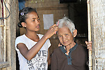 Srey Mao, 14, combs the hair of her grandmother Nou in Khnach, a village in the Kampot region of Cambodia. Along with another sister, Srey Mao lives with and takes care of her aging grandmother. Her parents died of AIDS.