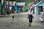 A woman walks along a street in Batey Bombita, a community in the southwest of the Dominican Republic whose population is composed of Haitian immigrants and their descendents.