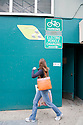 Woman walking by City CarShare (car rental service), bicycle parking, and electric vehicle charging station signs on the side of a public parking garage. California, USA