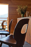 Simple contemporary chairs blend with the refurbished wood-lined interior of the kitchen/dining area