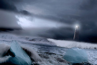 Lighthouse in Iceland seen from the coast with large waves and big icebergs in the forefront.
