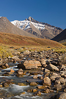 Autumn colors decorate the tundra, mountain stream, Brooks range mountains, arctic, Alaska.
