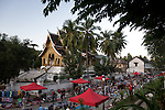 A temple and street market in the historic ancient city of Luang Prabang, Laos. Luang Prabang is a UNESCO World Heritage Site.
