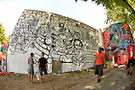 "Huntington, New York, U.S. 24th August 2013. Three world renowned street artists are decorating with graffiti the rear walls of the Hunting Arts Council building, at the art event ""Off the Walls"" Block Party, by SPARKBOOM, a project the council created to help emerging artists, showcase talents, and help its artistic family network. Taken with 180 degree fisheye lens."