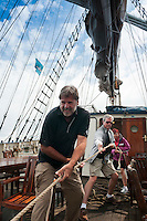 Ireland, July 2013. Guests learning the ropes. It is the first time that Tallship Thalassa, a barquentine sailing vessel with 3 masts, sails from Belfast to Galway along the Irish coastline. While a full-rigged ship is square-rigged on all three masts, and the barque is square-rigged on the foremast and main, the barquentine extends the principle by making only the foremast square-rigged. The advantages of a smaller crew, good performance before the wind and the ability to sail relatively close to the wind while carrying plenty of cargo made it a popular rig at the end of the 19th century. Photo by Frits Meyst/Adventure4ver.com