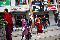 Buddhist monks mingle with other people showing a mix of traditional and western style dress at the main market in Thimphu.