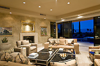 Contemporarty decore living room with beige couches and chairs in front of fire place and pocket doors that open to the outside