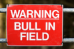"red ""warning bull in field"" sign on farm gate"