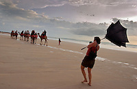 Sadie Quarrier armed with camera and wind-blown umbrella as  Camel Caravan gives tourists a ride at Cable Beach at sunset.<br /> Broome is one of the few tourist centers that actually has visitors during the wet.  The camel rides are prominently displayed on the travel brochures.<br /> Broome has 15,000 regular residents, but swells to 100,000 in tourist season.