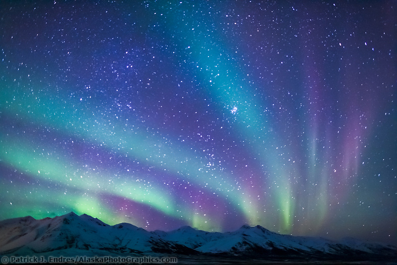 Colorful aurora borealis over the mountains near Chandalar Shelf, Brooks Range Alaska, hovering over the Arctic National Wildlife Refuge.