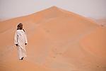 A man alone on the sand dunes of the Empty Quarter, Ar Rub Al Khali, Oman.