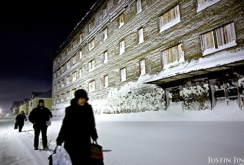 People walk by an empty boarding house in Vorkuta. The city&rsquo;s population has fallen by a third since the break-up of the Soviet Union, when subsidies for the Far North were slashed.<br /> Vorkuta is a coal mining and former Gulag town 1,200 miles north east of Moscow, beyond the Arctic Circle, where temperatures in winter drop to -50C. <br /> Here, whole villages are being slowly deserted and reclaimed by snow, while the financial crisis is squeezing coal mining companies that already struggle to find workers.