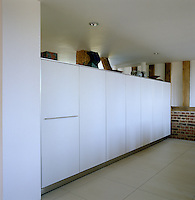 A bank of cupboards in the open-plan dining area provide plenty of storage as well as acting as a partition