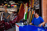 A Moroccan man sewing an awning on the machine in the awning manufacture in Marrakech, Morocco, 14 June 2007.