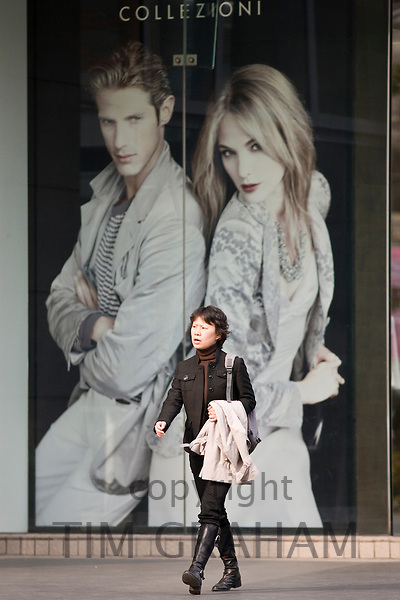 Chinese woman passes Western designer advertising poster in shopping street Nanjing Road, Shanghai, China