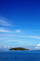 Small remote tropical island surrounded by deep blue water and sky.