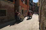 Two men pulling rubbish carts in Venice alleyway. Venice Italy.