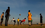 Locals train on a dirt pitch outside the Dobsonville Stadium in Soweto while the Brazilian natoinal team  train inside the stadium next door. During the FIFA World Cup in South Africa. Friday 4th June 2010. Photo: (Steve Christo)