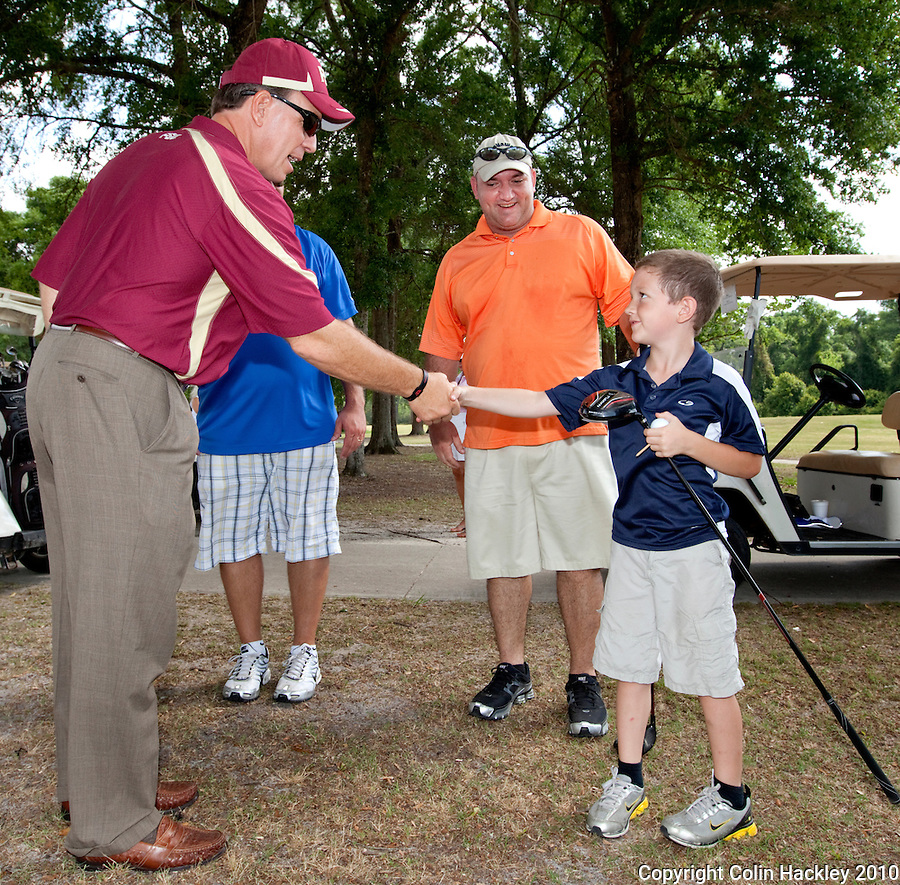 CRAWFORDVILLE, FLA. 5/22/10-FISHER 52210 CH-Florida State Head Coach Jimbo Fisher, left, greets Quinton Almand, age 7 of Tampa, his father Hubert and friend Logan Sherman, age 11 of Tampa, right, during the final stop of the 2010 Jimbo Fisher Coaches Tour & Legends Golf Tournament Saturday in Crawfordville. ..COLIN HACKLEY PHOTO
