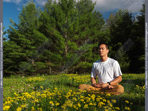 Asian man meditating outdoors during sunrise in the nature, sitting cross-legged in green outdoor summer nature scenery. Buddhist meditation. Instructor Shi Chang Dao, Toronto Shaolin Temple STQI.
