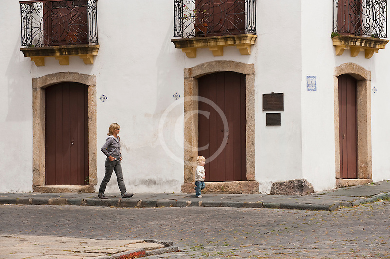 Uruguay, Colonia del Sacramento, Woman walking, cobbled street, Historic District