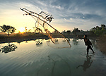 Siv Tom throws a fishing net at sunrise in the Cambodian village of O Kroich. The people of this village are from the Kouy indigenous group.