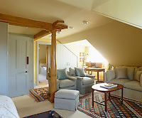 Contemporary wooden roof support designed by David Linley in this otherwise traditional attic bedroom with small seating area