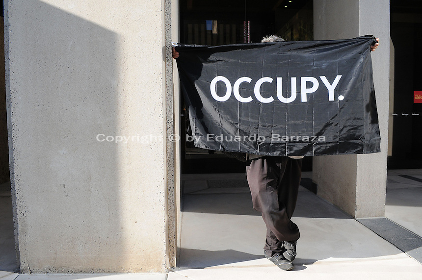 """Phoenix, Arizona. September 17, 2012 - A small crowd of demonstrators in Phoenix, Arizona gathered to mark one year since the beginning of the Occupy Movement that opposes Wall Street and large corporations that represent the one percent who control wealth in the United States. In this photograph, a protester with the Occupy Phoenix Movement demonstrates against the Wells Fargo bank in Downtown Phoenix during the first anniversary of the Occupy Wall Street Movement. The man momentarily covered his face from the sunlight using the """"Occupy"""" banner he used to demonstrate. Photo by Eduardo Barraza © 2012."""