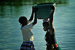 One woman helps another as they fetch water at the edge of Lake Malawi in Karonga, a town in northern Malawi. Fish from Lake Malawi, which is bordered by Malawi, Tanzania and Mozambique, provide an important part of people's diet in this area.