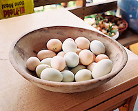 Wooden bowl of freshly collected chicken eggs