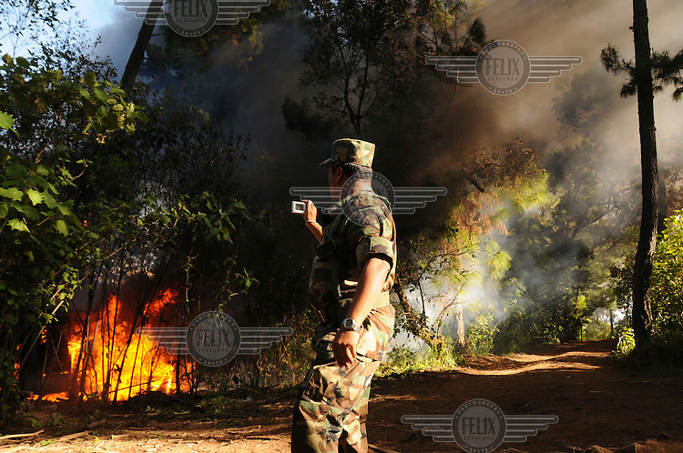 A soldier takes a photo as his regiment burn down a drugs laboratory discovered in a remote mountainous area. In recent years, the Sinaloa cartel and 'La Familia de Michoacan' cartel have turned to the production of the highly addictive drug crystal meth, also known as methamphetamine, metamfetamine or its street name 'Ice'. The production takes place in small laboratories in remote areas which are equipped with sophisticated equipment. ..