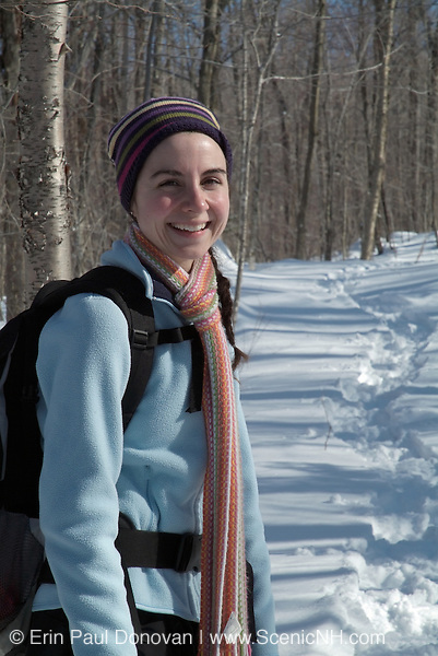 A adult female hiker wearing a scarf smiles for the camera while hiking on Starr King Trail in the White Mountains, New Hampshire USA