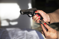 "USA. Arizona state. Scottsdale. Carrie Lightfoot is the founder and CEO of ""The Well Armed Woman. Where the Feminine and Firearms Meet"" which sell online resources for women gun owners. She stands in her bedroom and holds a handgun SIG SAUER P238 .38 in her hands. The SIG SAUER P238 .380 Auto Pistol features a stainless-steel slide with slide serrations and an anodized alloy beavertail-style frame. The single-action pistol has an extended 7-round magazine capacity. Carrie Lightfoot has finished loading the gun with bullets and is ready to used it as concealed carry firearm. Her shadow holding the gun is on the wall. A firearm is a portable gun, being a barreled weapon that launches one or more projectiles often driven by the action of an explosive force. Most modern firearms have rifled barrels to impart spin to the projectile for improved flight stability. The word firearms usually is used in a sense restricted to small arms (weapons that can be carried by a single person). The right to keep and bear arms is a fundamental right protected in the United States by the Second Amendment of the Bill of Rights in the Constitution of the United States of America and in the state constitutions of Arizona and 43 other states. 28.01.16 © 2016 Didier Rue"