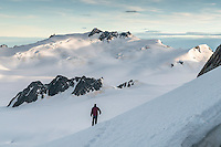 Climber walking in snow at Centennial Hut on top of Franz Josef Glacier. Mackay Rocks in centre left, Westland National Park, West Coast, New Zealand