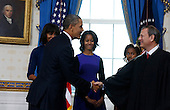 United States President Barack Obama shakes hands with Chief Justice John Roberts as he takes the oath of office at the official swearing-in ceremony in the Blue Room of the White House Sunday, Jan. 20, 2013. Administering the oath is Supreme Court Chief Justice Roberts. First lady Michele Obama and Malia and Sasha Obama look on..Credit: Larry Downing / Pool via CNP