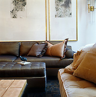In the living room of a New York town house a series of large gilt-framed prints hangs above a brown silk-covered sofa