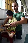 Nguyen Hong Loi, 24, cares for a child born without eyes in the Agent Orange children's ward of Tu Du Hospital in Ho Chi Minh City, Vietnam.  About 500 of the 60,000 children delivered each year at the maternity hospital, Vietnam's largest, are born with deformities, some because of Agent Orange, according to doctors. May 1, 2013.