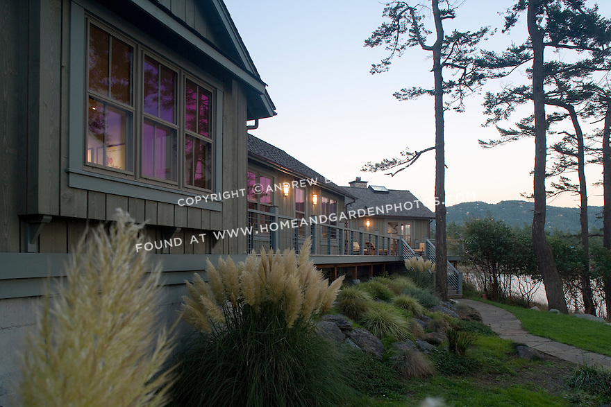 The windows of this waterfront home reflect the colors of the sunset. this image is available through an alternate architectural stock image agency, Collinstock located here: http://www.collinstock.com