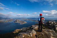 Female hiker enjoys view from the summit of Stornappstind (740m), Flakstadøy, Lofoten Islands, Norway
