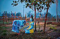 A Lady praying in front of a statue of Lord Shiva near the ghats during the Kumbh Mela in Haridwar, 2010.