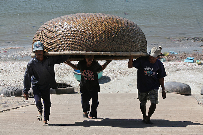 Three men carry a traditional woven bamboo fishing boat up the harbor steps in Mui Ne, Vietnam. Nov. 20, 2011.
