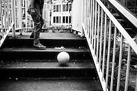 A boy chases his football down the steps of an overpass in downtown Yangon, Myanmar.