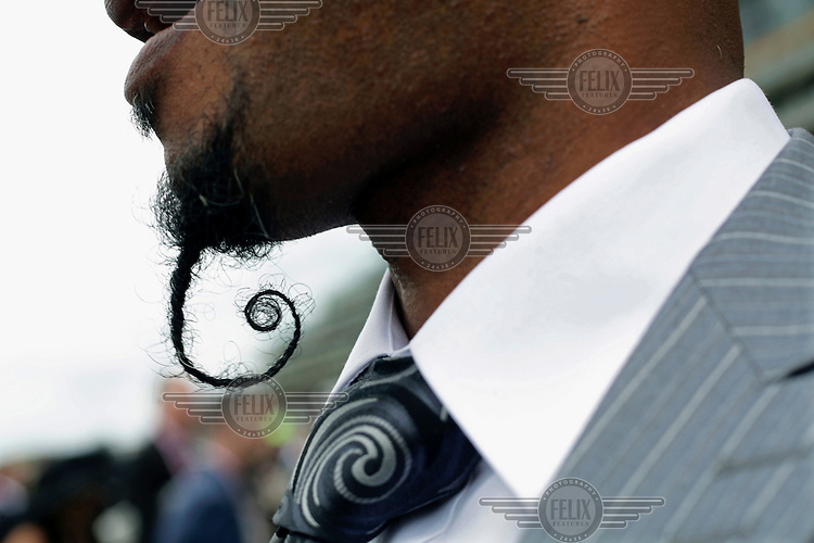 A man sporting an ornate goatee beard watches a race at the Royal Ascot race metting. The annual event, during which each day begins with the Queen's arrival in a horse drawn carriage, dates back to 1711 when Queen Anne organised the first races on what was then a heath near Windsor Castle.