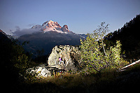 Stephanie Maureau bouldering on a clear evening at the Col de Montets with Aig. Verte in the background.