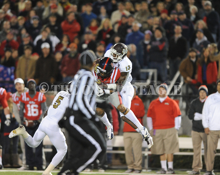 Ole Miss wide receiver Donte Moncrief (12) makes a 42 yard reception in the first quarter as Mississippi State defensive back Johnthan Banks (13) and Mississippi State defensive back Nickoe Whitley (5) defend at Vaught Hemingway Stadium in Oxford, Miss. on Saturday, November 24, 2012. Ole Miss won 41-24.