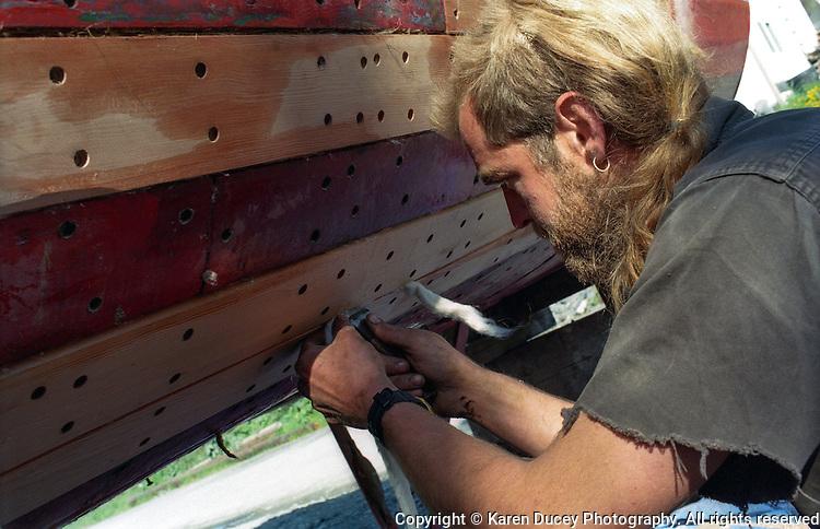 Fisherman Tim Robb caulks a boat in Kodiak, Alaska.