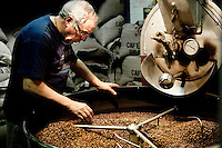 Man sorting through freshly roasted coffee beans, Sant Eustachio Cafe, Rome, Italy